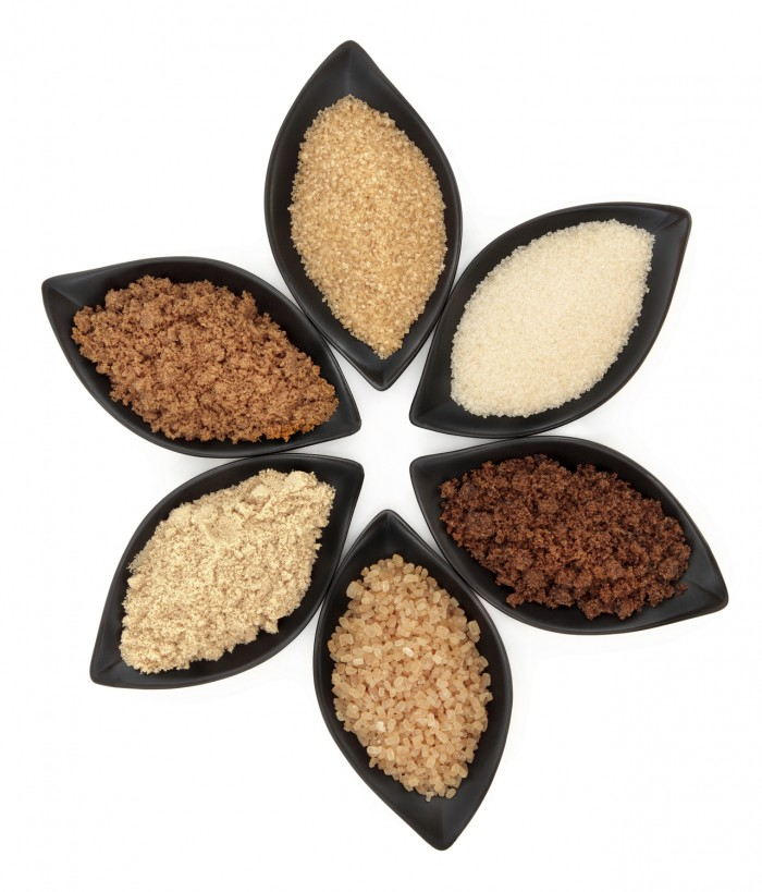Selection of demerara granulated, molasses, muscovado, crystal and light brown sugar in black leaf shaped dishes over white background.