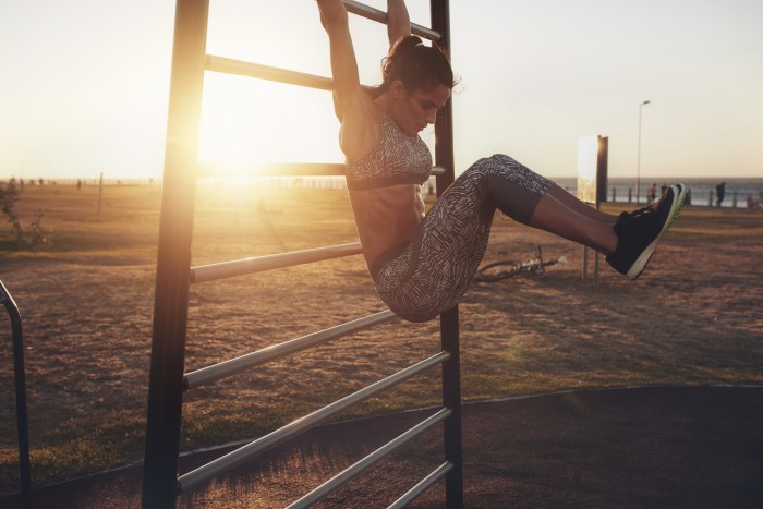 Outdoor shot of healthy young woman exercising on wall bars during sunset.  Strong woman doing stretching and looking at camera.
