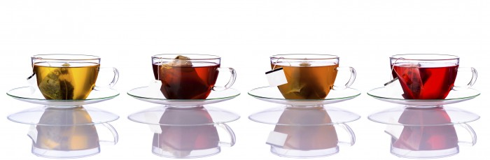 Collage of four Tea cups with tea-bags isolated on white background