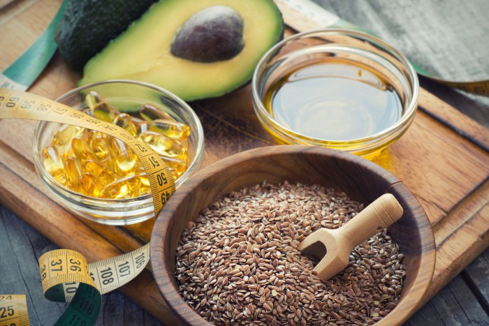 Sources of omega 3 fatty acids: flaxseeds, avocado, oil capsules and flaxseed oil