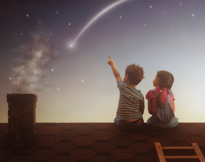 Two cute children sit on the roof and look at the stars. Boy and girl make a wish by seeing a shooting star.