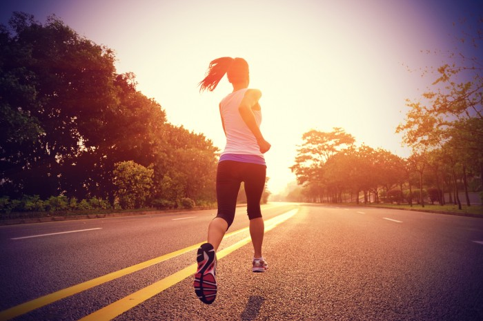 Young woman runs on an empty road as her brunette ponytail swings in the air.  The young athlete wears sturdy athletic shoes with pink and black soles.  Both sides of the divided road feature green grassy areas with numerous shade trees.