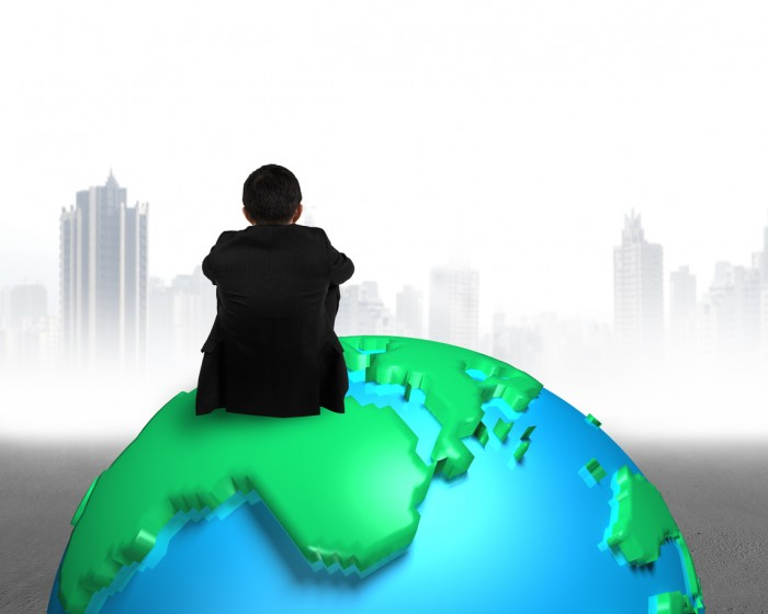 businessman sitting on 3d map globe watching gray buildings cityscape
